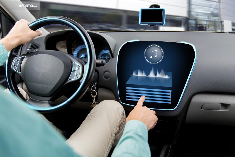 Foto pengemudi mengoperasikan fitur hiburan di mobil