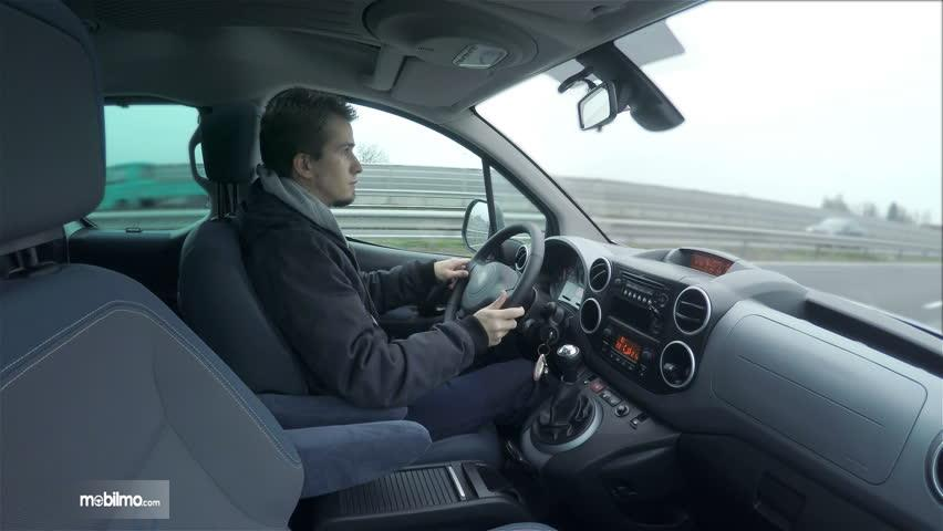 Seorang pengemudi memakai jaket AC mobil terlalu dingin