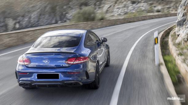 Gambar ini menunjukkan sebuah mobil warna biru melaju sendiri di jalan