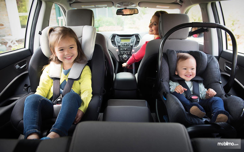 Foto dua orang anak naik mobil duduk di kursi khusus
