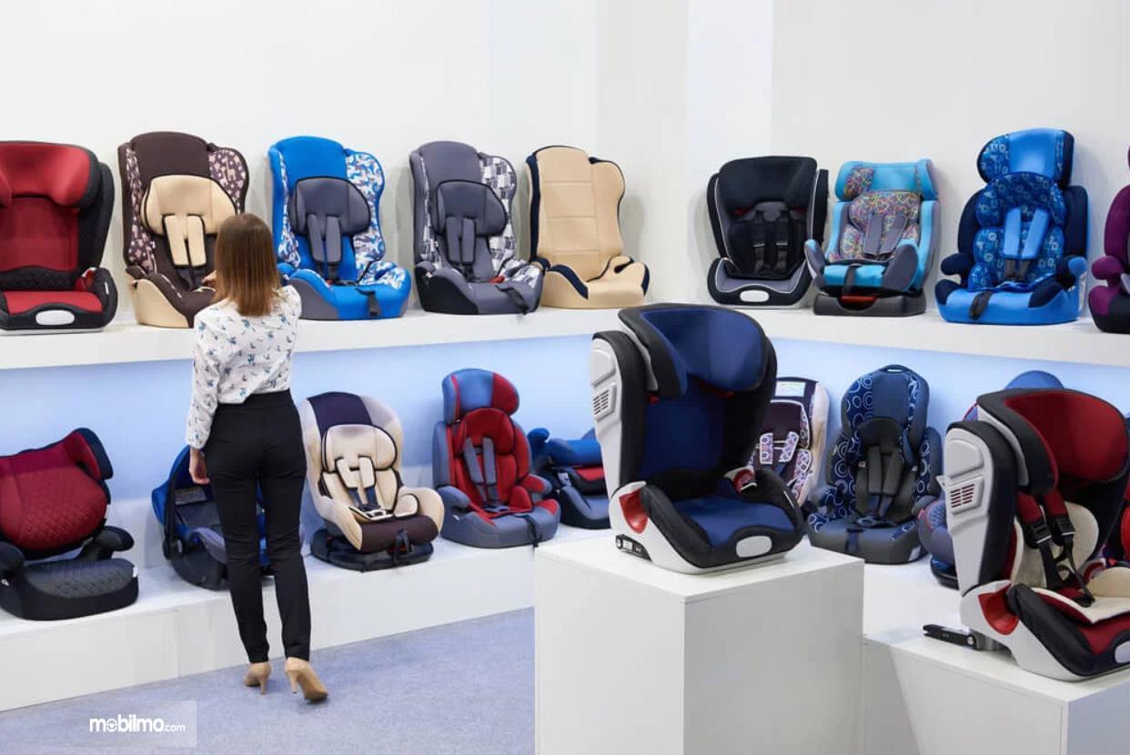 Foto seorang ibu sedang memilih-milih Child Car Seat di sebuah toko