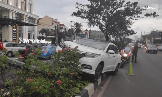 Gambar ini menunjukkan sebuah mpobil putih terjadi kecelakaan