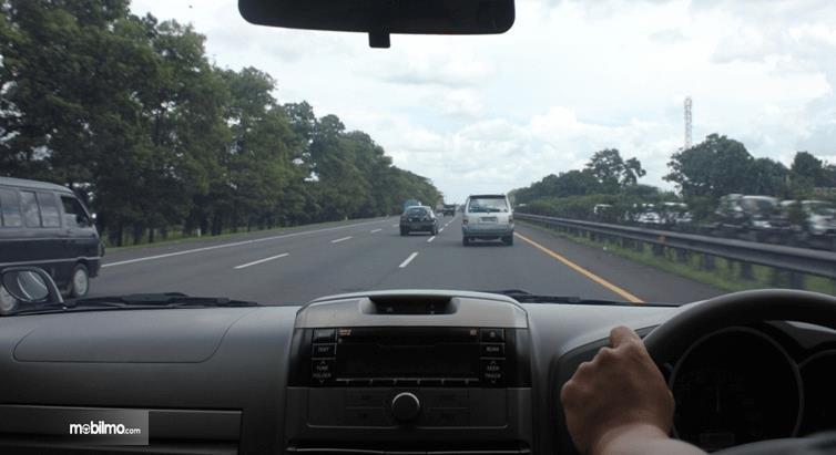 Gambar ini menunjukkan seseorang pengemudi sedang melaju di jalanan