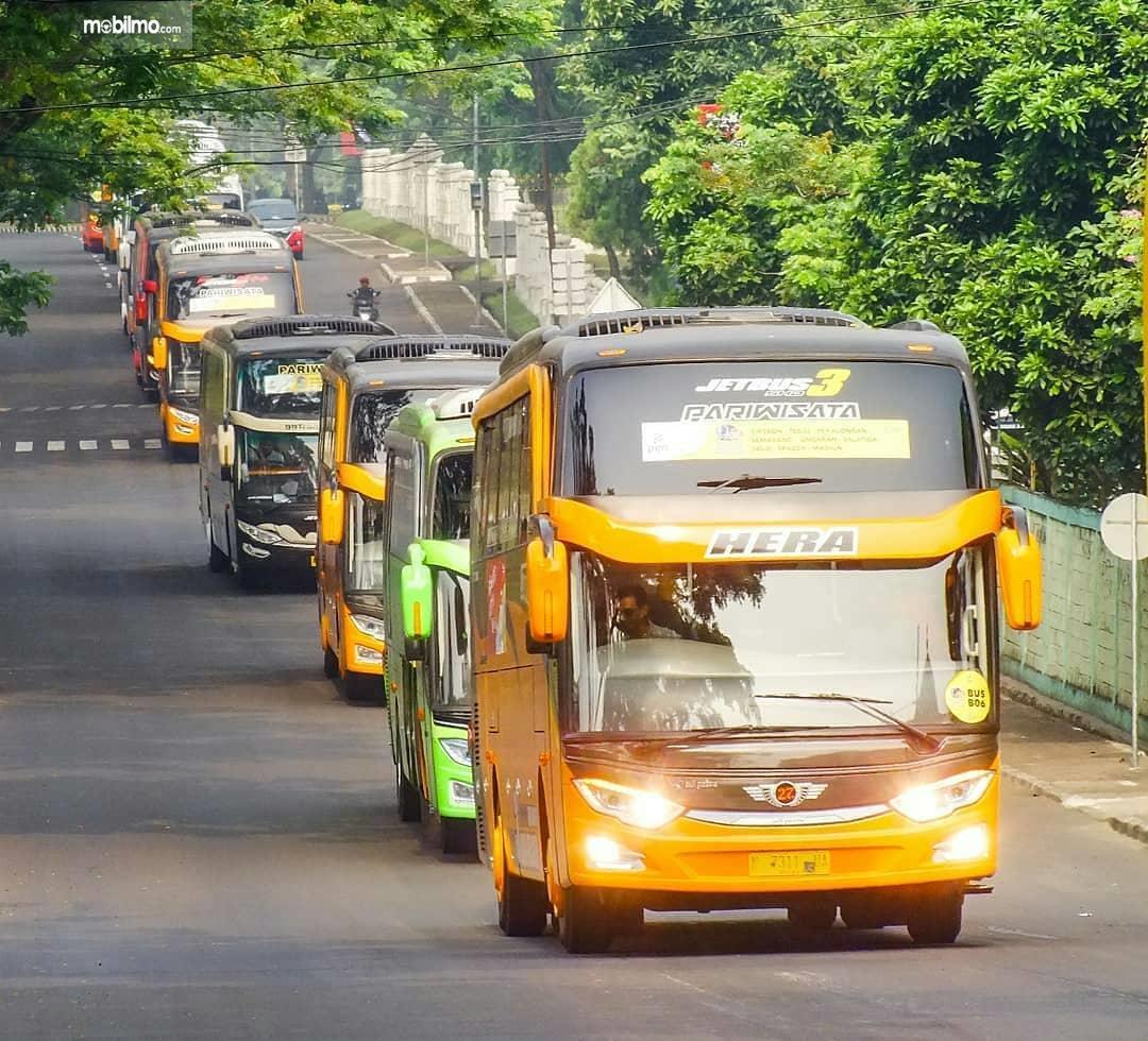 Armada bus mudik bareng beriringan melintas di jalan raya