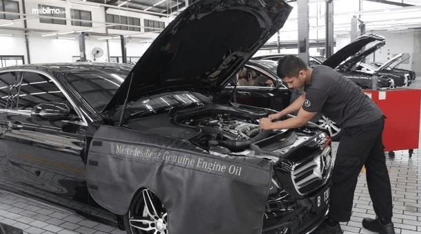 Gambar ini menunjukkan seorang pria sedang melihat mesin mobil Mercedes-Benz