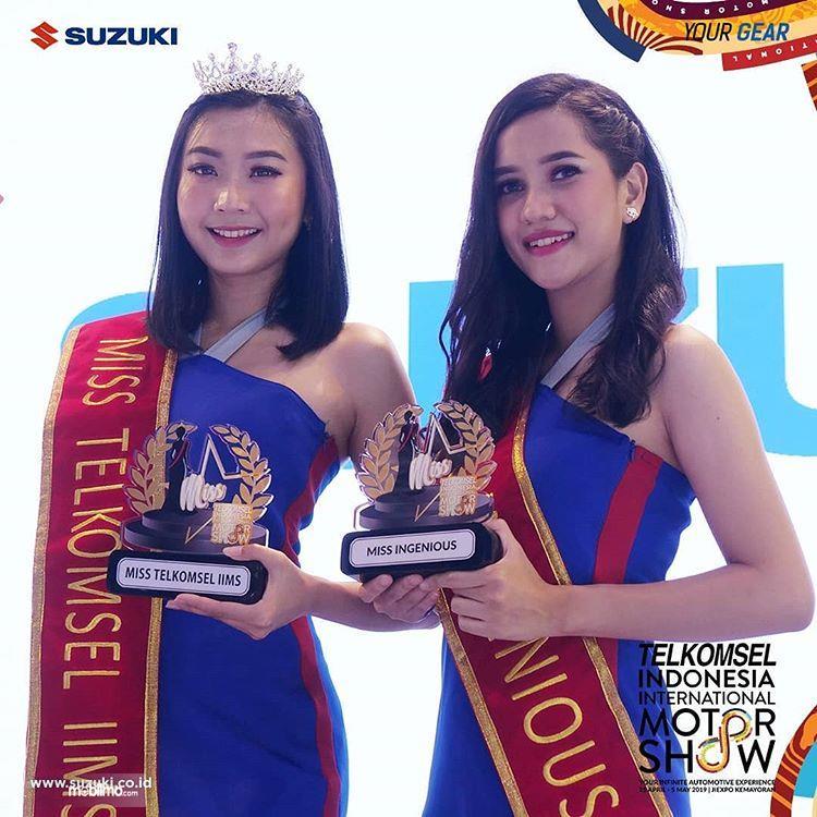 Dua gadis Suzuki Aria menunjukkan penghargaan yang diraih di pameran Telkomsel IIMS 2019