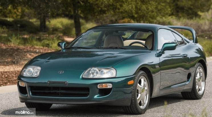 Gambar ini menunjukkan mobil Toyota Supra 1997 dengan warna hijau tampak bagian depan