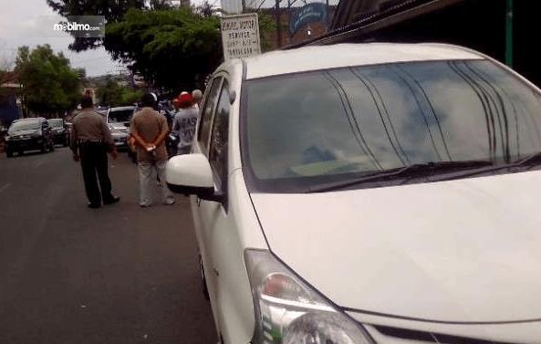 Gambar ini menunjukkan mobil putih yang menepi dan banyak orang di belakangnya