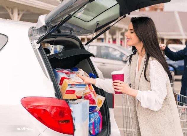 Gambar ini menunjukkan seorang wanita memasukkan camilan dan barang ke dalam bagasi