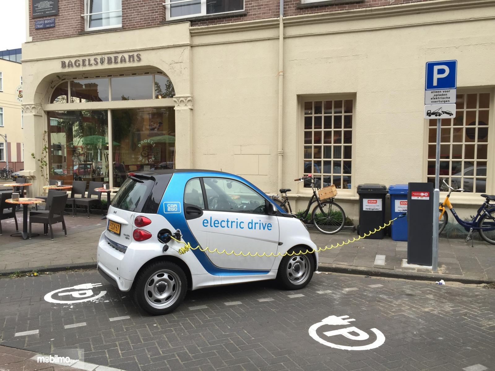Gambar mobil listrik sedang melakukan pengisian daya di stasiun pengisian