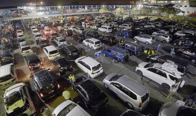 Gambar ini menunjukkan banyak mobil sedang melaju berjejer di jalanan