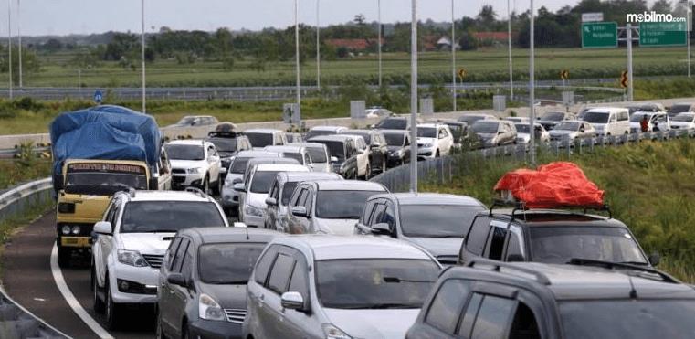 Gambar ini menunjukkan jalanan yang penuh dengan mobil karena macet