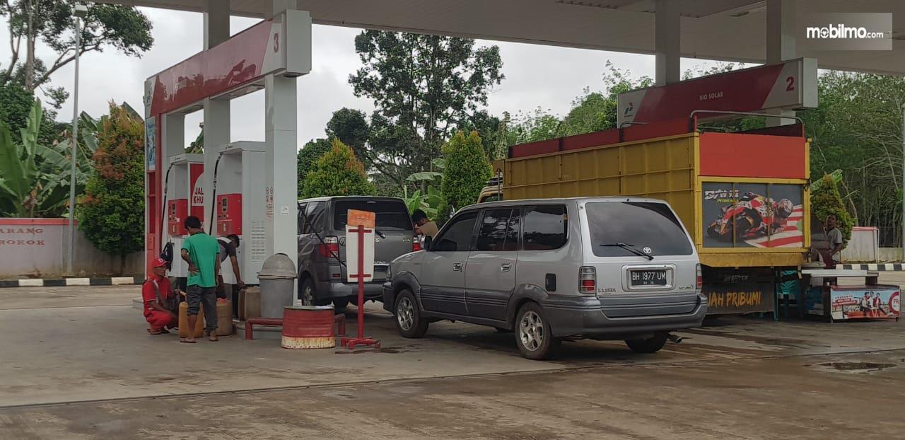 Gambar menunjukkan mobil sedang mengisi BBM di SPBU