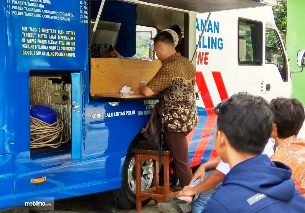 Beberapa orang sedang mengantre melakukan perpanjangan SIM melalui layanan SIM Keliling