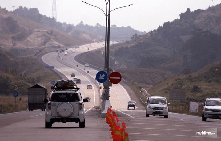 Gambar ini menunjukkan beberapa mobil sedang melaju di jalanan menurun dan akan menanjak
