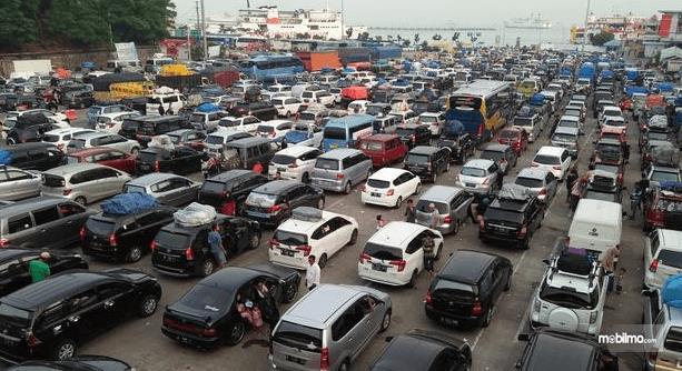 Gambar ini menunjukkan banyak mobil sedang mengantri di pelabuhan Merak