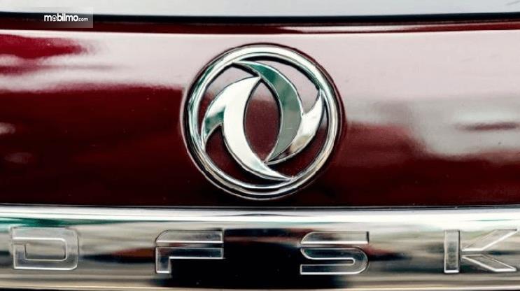 Gambar ini menunjukkan logo DFSK pada mobil warna merah