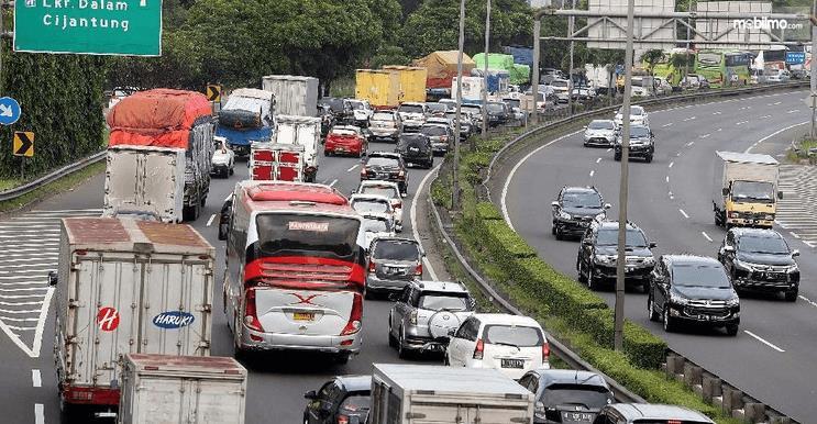 Gambar ini menunjukkan banyak mobil sedang terjebak kemacetan di jalan tol
