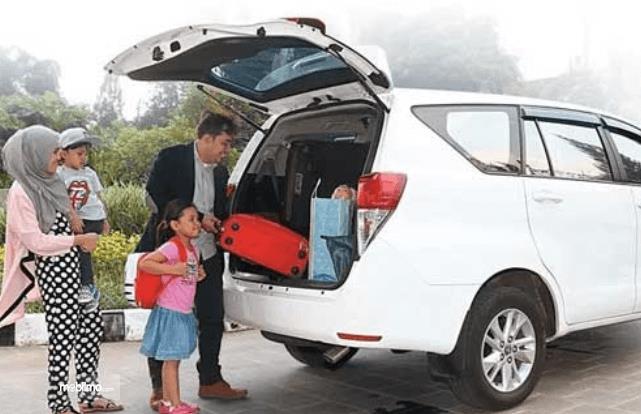 Gambar ini menunjukkan sebuah keluarga sedang memasukkan barang ke dalam mobil warna putih