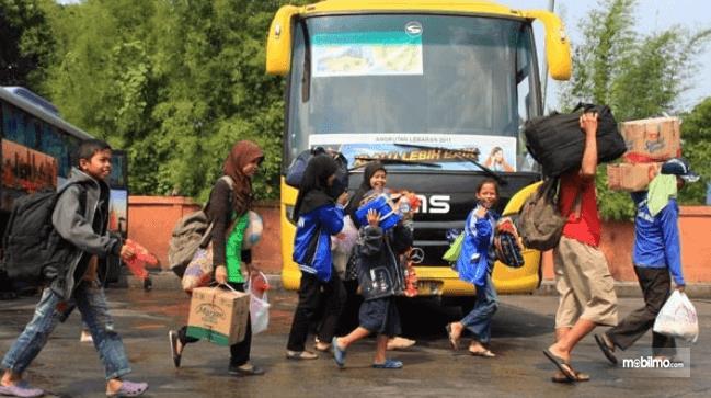 Gambar ini menunjukkan banyak orang sedang berjalan di depan bus