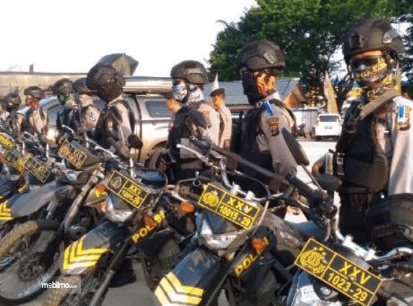 Gambar ini menunjukkan banyak polisi dengan sepeda motornya