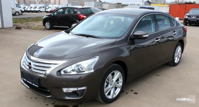 Gambar ini menunjukkan mobil Nissan Teana warna hitam tampak samping kiri dan depan