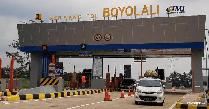 Gambar ini menunjukkan gerbang tol Boyolalu dan terdapat mobil warna putih tampak depan