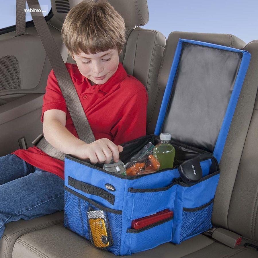 Foto menunjukkan seorang anak sedang memeriksa bekal makanannya di mobil