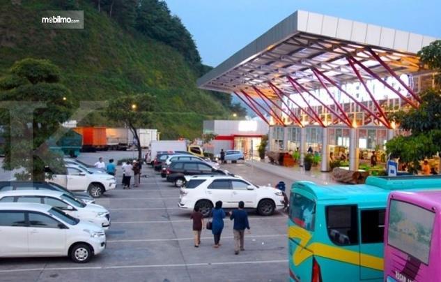 Gambar ini menunjukkan kondisi rest area dengan beberapa orang dan mobil yang terparkir