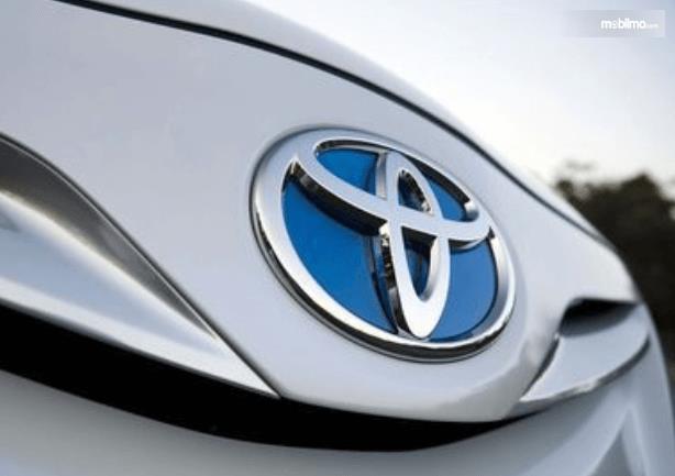 Gambar ini menunjukkan Logo Toyota pada mobil warna putih