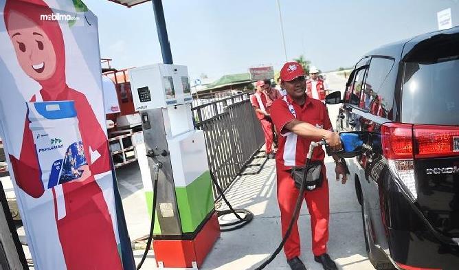 Gambar ini menunjukkan seorang petugas SPBU di rest area sedang mengisi bahan bakar