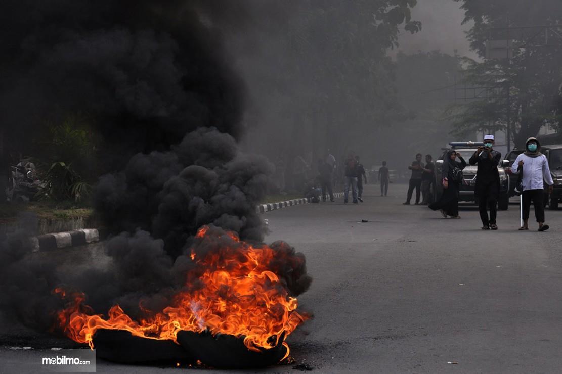 Foto menunjukkan demonstran membakar ban mobil di tengah jalan