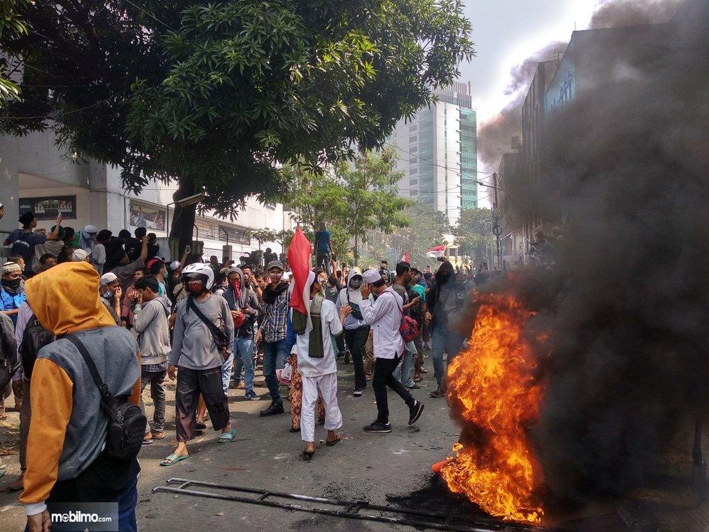 Foto menunjukkan ban yang dibakar oleh demonstran menciptakan kepulan asap hitam pekat