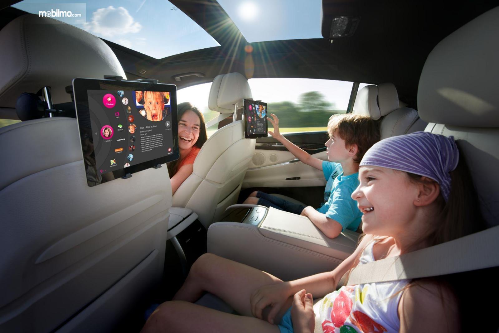 Foto penumpang anak-anak menikmati hiburan di dalam mobil