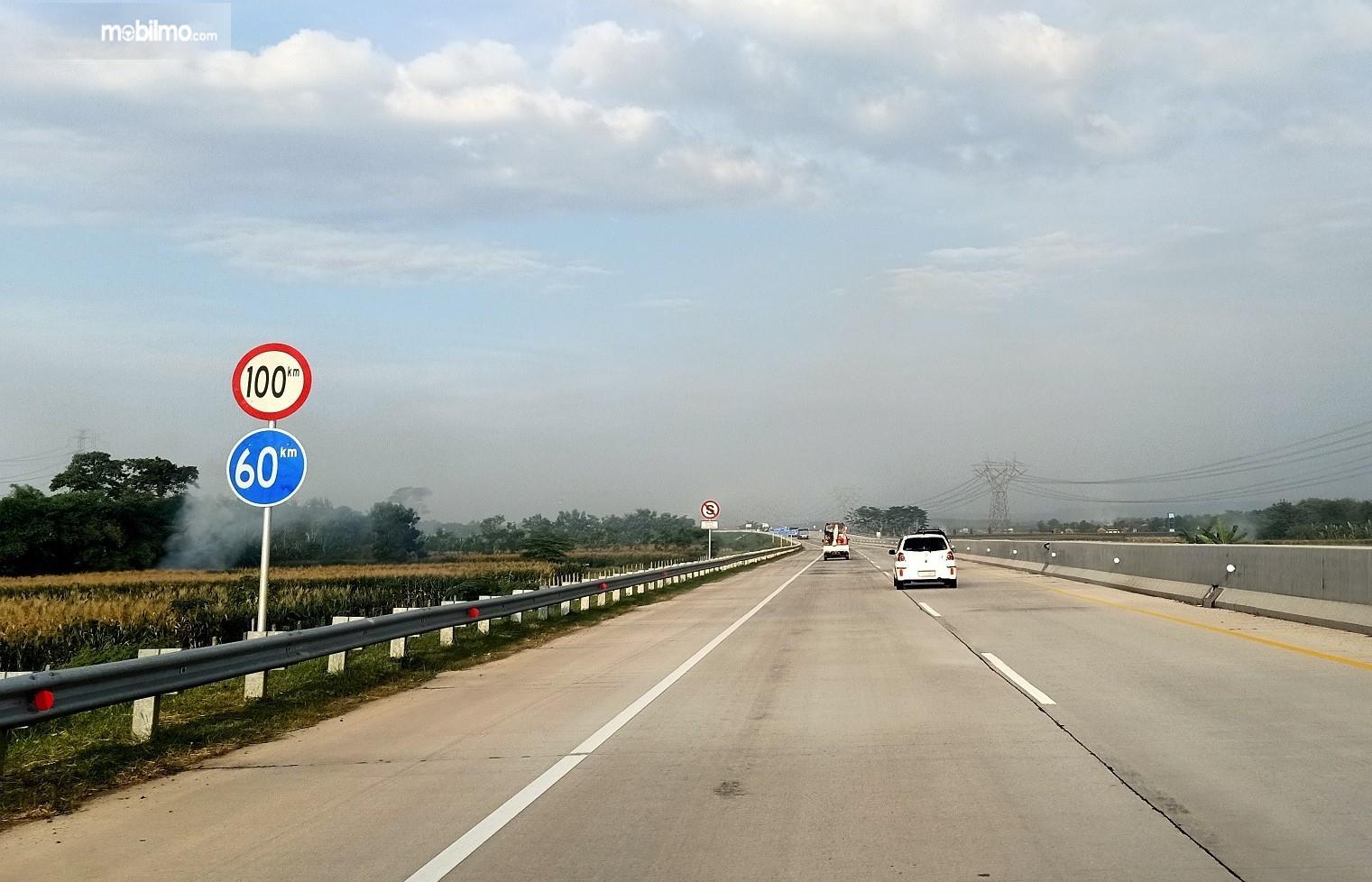 Foto jalan Tol Trans Jawa yang lengang lengkap dengan rambu-rambu batas kecepatan