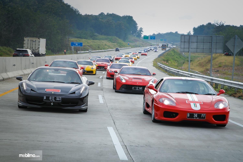 Foto menunjukkan puluhan mobil Ferrari melaju di jalan Tol Trans Jawa