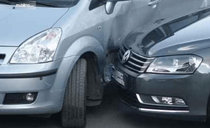 Gambar ini menunjukkan 2 mobil saling berbenturan