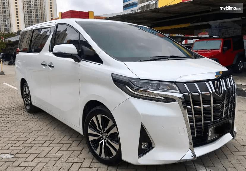 Gambar ini menunjukkan Toyota Alphard warna putih tampak depan