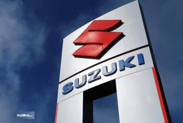 Gambar ini menunjukkan Logo Suzuki dengan warna merah dan tulisan Suzuki warna biru