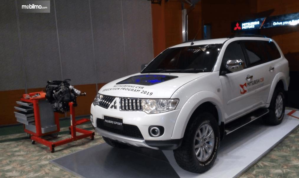 Gambar ini menunjukkan mobil Mitsubishi Pajero Sport warna putih dan disampingnya ada mesin