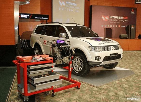 Gambar ini menunjukkan sebuah mesin dan terdapat mobil Mitsubishi Pajero Sport