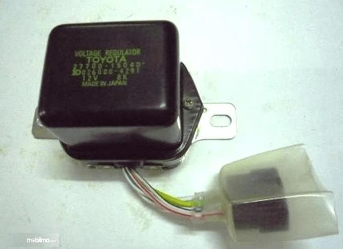 Gambar ini menunjukkan voltage regulator warna hitam