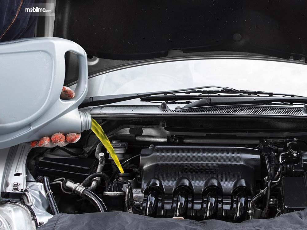 Foto menunjukkan seseorang sedang melakukan ganti oli mobil