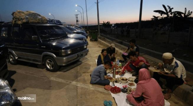 Gambar ini menunjukkan beberapa orang sedang makan bersama di depan kendaraan