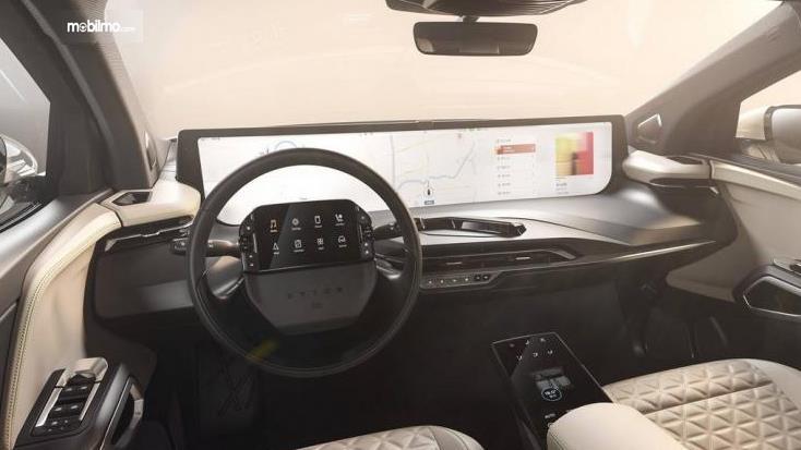 Gambar ini menunjukkan dashboard mobil dan kemudi dengan layar ukuran besar