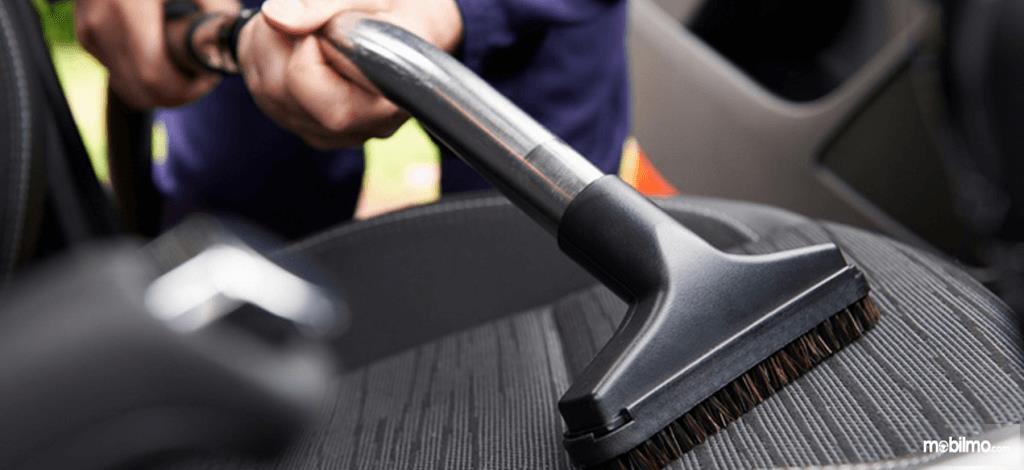 Foto seseorang sedang vacuum jok mobil