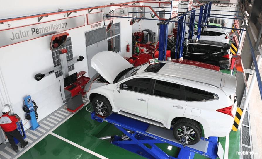 Gambar ini menunjukkan beberapa mobil sedang pengecekan di dalam diler Mitsubishi