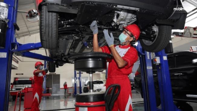 Gambar ini menunjukkan beberapa mekanik sedang merawat rangka mobil