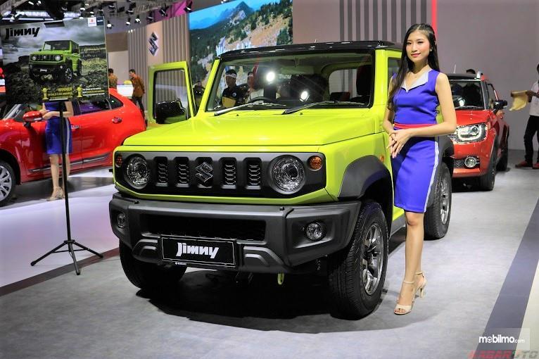 Foto menunjukkan seorang model berpose bersama Suzuki Jimny di sebuah pameran otomotif