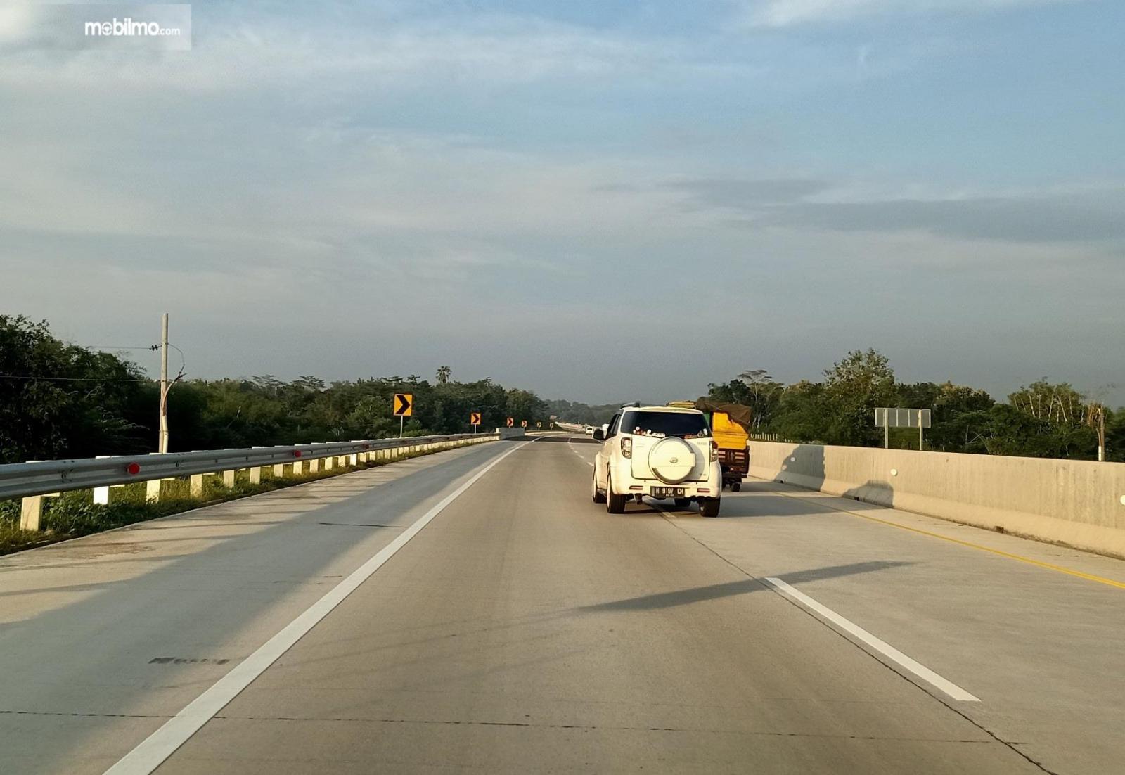Foto menunjukkan mobil menyalip melalui lajur kiri di jalan tol karena ada mobil berjalan pelan di lajur kanan